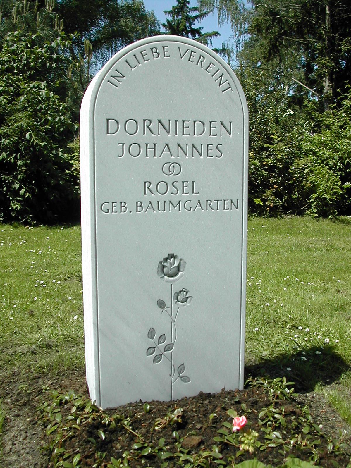 Grabmal aus griechischen Marmor, Bearbeitung gesandelt. Die Rose ist plastisch in der Fläche gearbeitet und anthrazit getönt, die Schrift ist keilvertieft gehauen und anthrazit getönt.