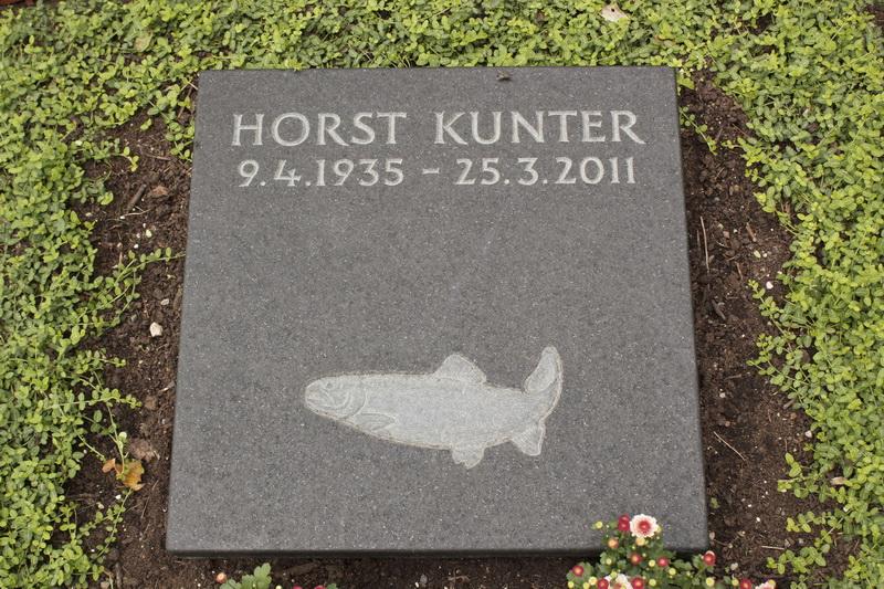 Grabplatte aus schwarzen schwedischen Granit. Die Forelle ist plastisch in der Fläche gearbeitet und hell getönt.