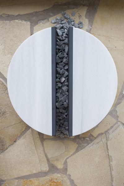 Grabplatte für Lebenspartner und Ehepaare. Der Stein wurde in zwei gleichgroße Hälften gegliedert. Die Form des Kreises verbindet beide Elemente wieder zu einem vollendeten Objekt.