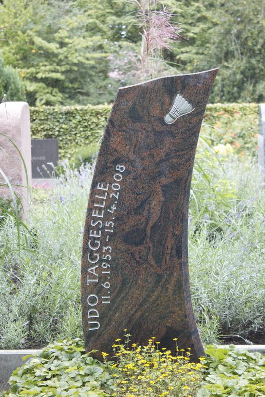 Grabmal aus Halmstad-Granit (Schweden). In der spannungsvoll geschwungenen Steinform wurde die Dynamik des Badmintonsports aufgegriffen und durch die versetzt im Bogen angeordnete Schrift noch verstärkt.