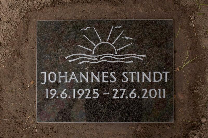 Grabplatte für ein Rasengrab. Afro-Granit. Oberfläche poliert. Motiv und Schrift sind keilvertieft ausgearbeitet und hellgrau ausgemalt.