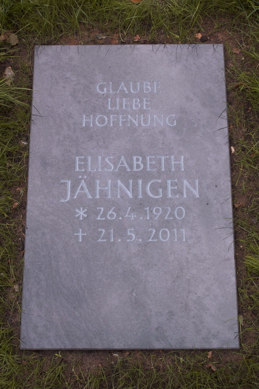 Grabplatte für ein Rasengrab.  Orion-Granit, Oberfläch poliert. Die Schrift ist keilvertieft eingearbeitet und hellgrau ausgemalt.