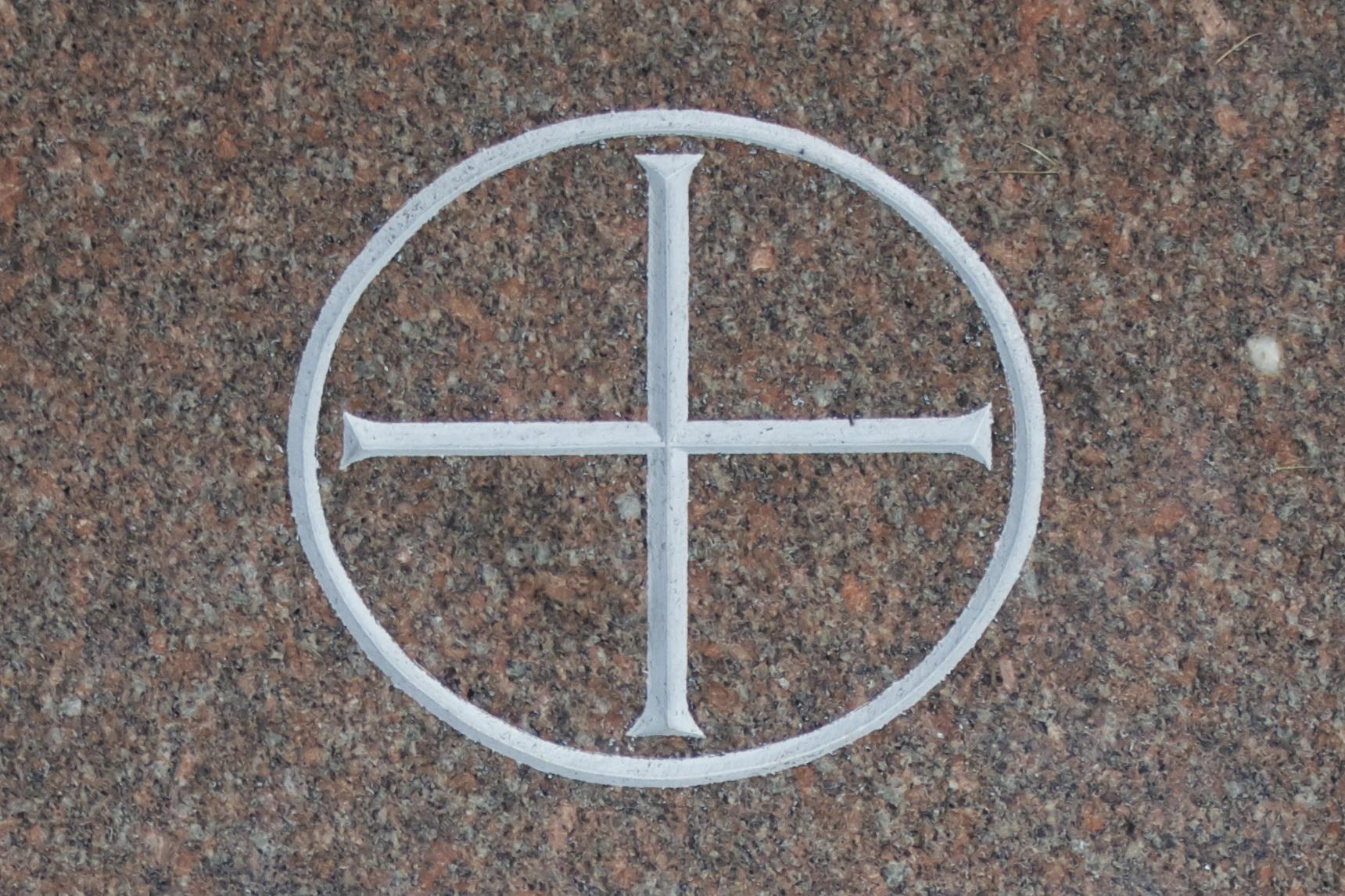 Kreuz mit Kreisscheibe als Symbol der Erde als Gottes Schöpfung.