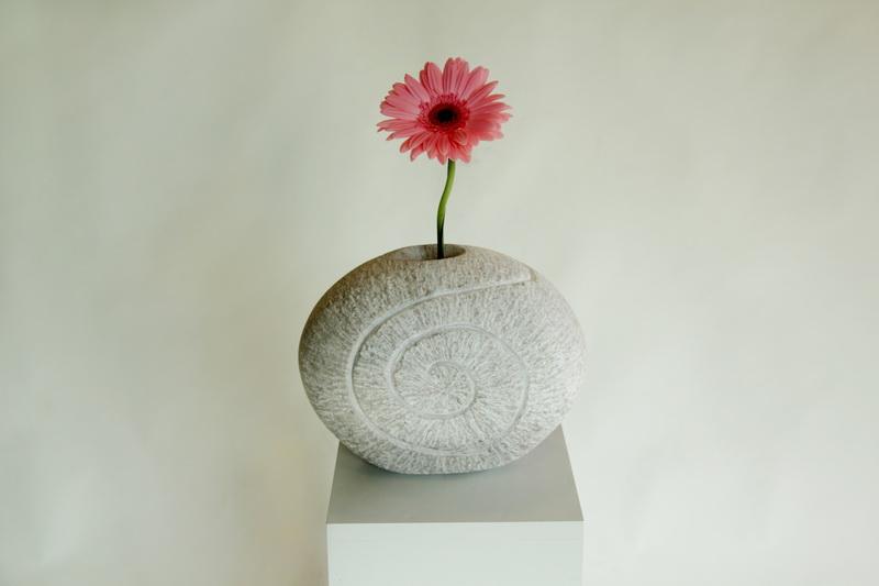 Vase aus brasilianischen Marmor. Von der Vorderseite aus schlängelt sich eine Spirale vorbei an der Blume auf die Rückseite der Vase.