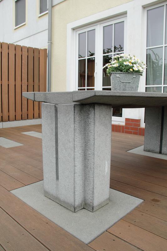 Die große Tischplatte ruht zwei massiven Auflagern. Durch ihre Dimensionen strahlen sie Ruhe und Beständigkeit aus.