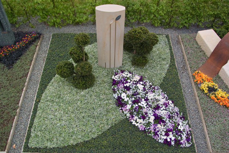 Ganzheitliche Grabgestaltung, die das Thema des Grabmals aufgreift.