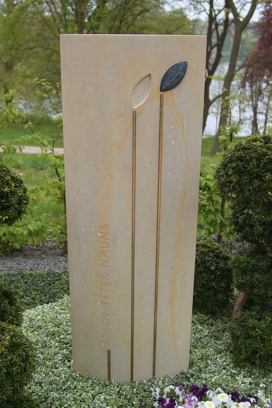 Die Gestaltung mit zwei stilisierten Blättern steht symbolisch für das Ehepaar. Ein Blatt ist dauerhaft in den Stein eingelassen, vom zweiten ist ein Abdruck zu sehen. Es verbleibt als Ritualstein bei der trauernden Person.