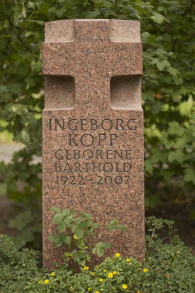 Grabmal mit kubischer Grundform für ein Urnengrab. Das obere Drittel des Steins ist als Würfelkreuz geformt. Granit Vanga (Schweden), Oberflächenbearbeitung geflammt, Kreuzflächen vom Hieb bearbeitet.